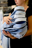Many men's shirts in the hands of women. Stock Photos