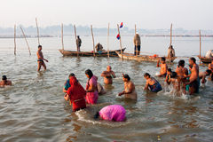 Many men and women bathe in holy river. Men and women bathing in cold Sangam water at time of celebration of Paush Purnima during the biggest festival Kumbh Mela Stock Photo