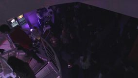 Many men, women walking up and down spiral stairs at nightclub. Stock footage stock video