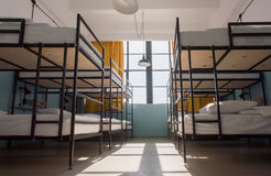 Many metal bunk beds in dorm room for twelve people at youth hostel Stock Images