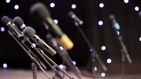 Many microphones on stage in the rays of twinkling lights stock video