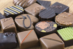 Many milk and dark chocolate candies on the wooden background Stock Images