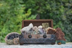 Many minerals quartz and crystal stones in wooden box. Against green nature background Stock Photos
