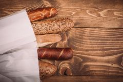 Many mixed baked breads and rolls on rustic wooden table. Top view Royalty Free Stock Photos