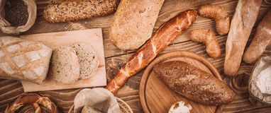 Many mixed baked breads and rolls on rustic wooden table. Top view Stock Photo