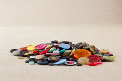 Pile of mixed buttons on hessian Royalty Free Stock Photo