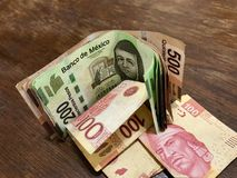 Many mixed Mexican peso bills spread over a wooden desk. Many mexican pesos bills spread over a wooden desk inside a small business office stock photography