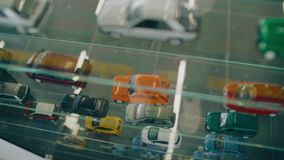 Many models of cars are on the glass case. Top view camera in motion stock footage