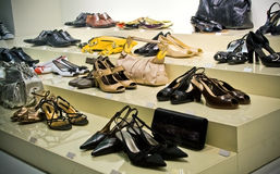 Many modern shoes on shop shelf. Many shoes and purses on store showcase stock photography
