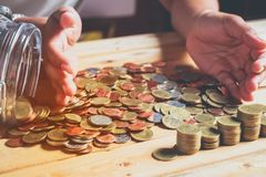Many money. Coins on the brown table .people`s hands on the table with many coins stock photo