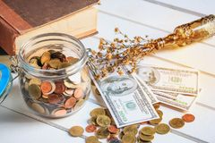 Many money coins in the glass bottle. Jar and some US dollar banknotes on the wood  floor Royalty Free Stock Photography