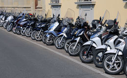 Many mopeds and motorcycles parked along the busy street Royalty Free Stock Images