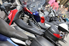 Many mopeds scooters and motorcycles parked Stock Photos