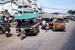 Many motorbikes with large covered trailers congregate on village street. In Cambodia Royalty Free Stock Photography