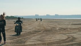 Many motorcyclists racing pursuit girl along the sandy beach from far away. Many motorcyclists racing along the sandy beach from far. Bikers column ride a stock video footage