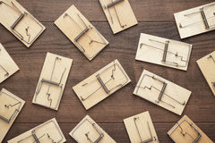 Many mousetraps on the wooden background. Many mousetraps on the brown wooden background Stock Image