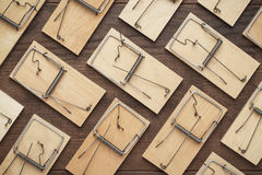 Many mousetraps on the wooden background. Many mousetraps in order on the brown wooden background Royalty Free Stock Images
