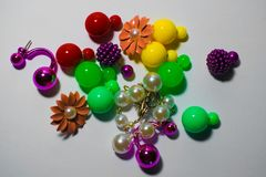 Many multi-colored earrings on a white background, in the form of balls and colors of metal and plastic. royalty free stock photography