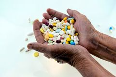 Many multi-colored pills in a Senior's hands on white background. Alzheimer's patients; caring for the health of the elderly patients stock photo