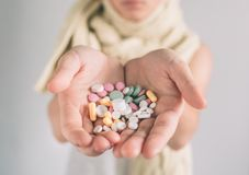 Many multi-colored pills in a woman hands on white background Royalty Free Stock Photo