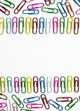 Many multi-colored stationery clips for documents and multi-colored pencils lie on a white background stock image