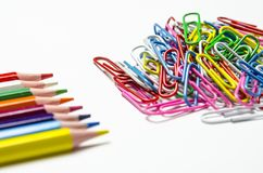 Many multi-colored stationery clips for documents and multi-colored pencils lie on a white background stock photo