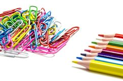Many multi-colored stationery clips for documents and multi-colored pencils lie on a white background. Close-up. top view royalty free stock photography