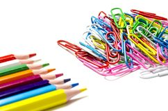 Many multi-colored stationery clips for documents and multi-colored pencils lie on a white background royalty free stock photos