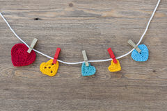 Many multicolor crochet hearts on wooden background for Valentines day Stock Image