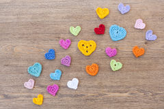 Many multicolor crochet hearts on wooden background for Valentines day Royalty Free Stock Image