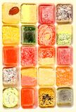 Many multicolored candies arranged in cells as a background. Twenty different candies laid in the cells as a background royalty free stock images