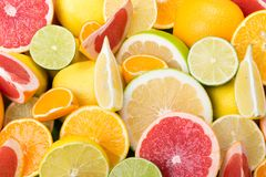 Many multicolored cut citrus fruits lie together as a background, grapefruit mandarin. Lemon Royalty Free Stock Images
