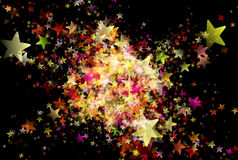Many multicolored flying stars on black background Royalty Free Stock Photos