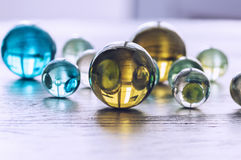 Many multicolored glass balls on a wooden surface. Royalty Free Stock Photography