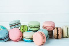 Many multicolored macaroons or macaron on a white wooden background close-up, copy space. Many multicolored macaroons or macaron on a white wooden background Stock Photography
