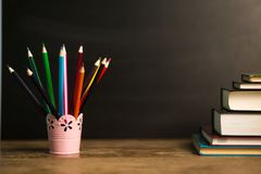 Many multicolored pencils in glass on wooden table with black background. Back to school concept stock images