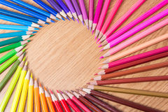 Many multicolored pencils on a wooden background. Round frame of different colored pencils with space for text. Copyspace. Royalty Free Stock Image