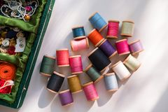 Many multicolored sewing threads on wooden coils are scattered stock images
