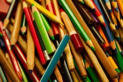 Multicolored sharpened coloring pencils on a pile. Many multicolored sharpened coloring pencils on a pile royalty free stock photo