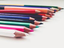 Many multicolored sharpened pencils lay on a white surface in a scattered state stock photography