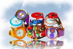 Many multicolored wristwatches folded by a slide stock images