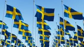 Many National flags of Sweden on flagpoles in front of blue sky. royalty free illustration