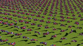Many national flags of the United Kingdom. Waving on wind in green field. Three dimensional rendering animation. View from above stock video footage