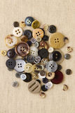 Pile of neutral brown buttons on hessian Stock Photos