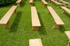 Many new wooden seats on grass Royalty Free Stock Photography
