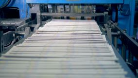 Newspaper sheets moving on a typography line, close up. Many newspaper sheets on a special line at a print office stock video footage