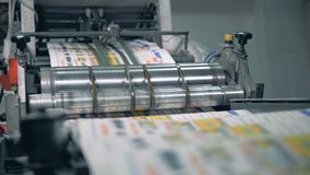 Many newspapers moving on typographic conveyor with a roller. 4K stock footage