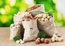 Many nuts in bags. On green background Stock Photo