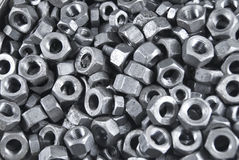 Many nuts with metallic luster. Many steel nuts with a bluish metallic luster Royalty Free Stock Images