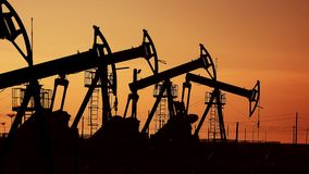 Many oil pumps at sunset under the red sky on industrial platform field with crude petroleum hydraulic extraction units stock footage